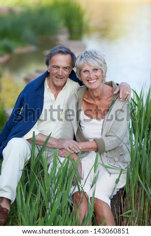 Portrait of happy loving senior couple sitting by lakeside in park - stock photo