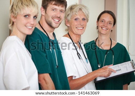 Portrait of happy male and female doctors standing in hospital - stock photo