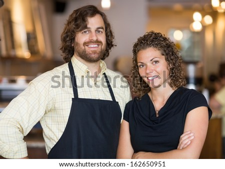 Portrait of happy male and female owners standing together in coffee shop - stock photo