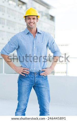 Portrait of happy male architect with hands on hips outdoors - stock photo