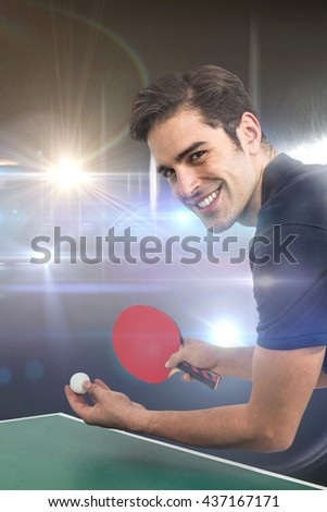 Portrait of happy male athlete playing table tennis against american football arena - stock photo