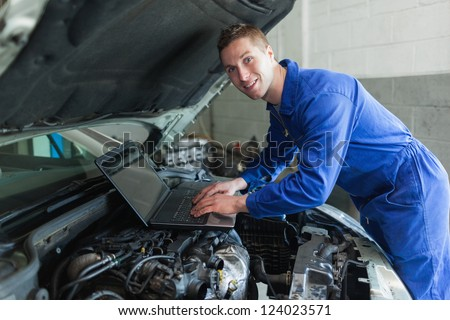Portrait of happy male auto mechanic using laptop - stock photo