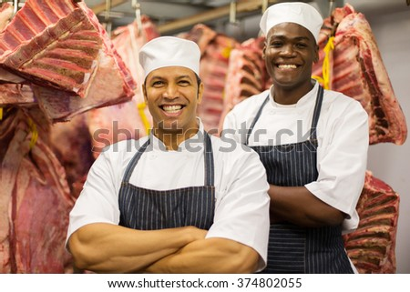 portrait of happy male butchers standing in front of raw meat - stock photo