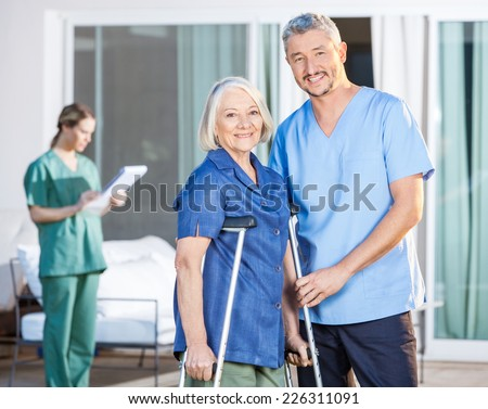 Portrait of happy male caretaker and disabled senior woman with female nurse in background at nursing home yard - stock photo