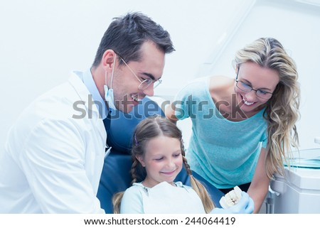Portrait of happy male dentist with assistant and little girl - stock photo