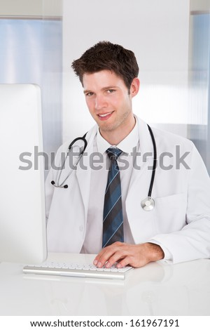 Portrait Of Happy Male Doctor Using Computer At Desk In Clinic - stock photo