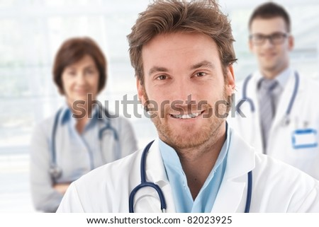 Portrait of happy male doctor with colleagues behind.? - stock photo