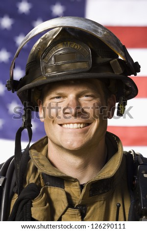 Portrait of happy male firefighter against American flag - stock photo