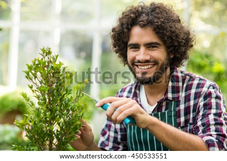 Portrait of happy male gardener pruning plants at greenhouse - stock photo