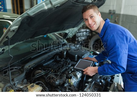 Portrait of happy male mechanic by car holding digital tablet