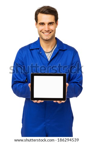 Portrait of happy male mechanic displaying digital tablet over white background. Vertical shot. - stock photo