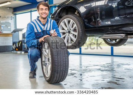 Portrait of happy male mechanic pressing gauge into tire tread to measure its depth at garage - stock photo