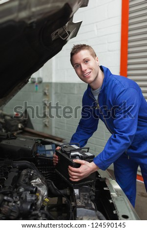 Portrait of happy male mechanic with battery by car - stock photo