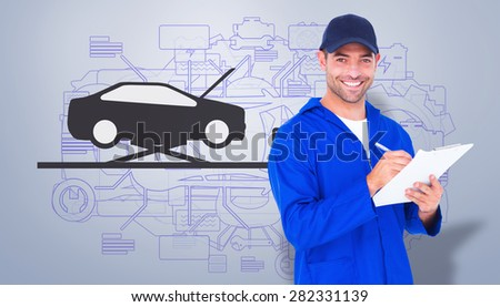 Portrait of happy male mechanic writing on clipboard against grey vignette - stock photo