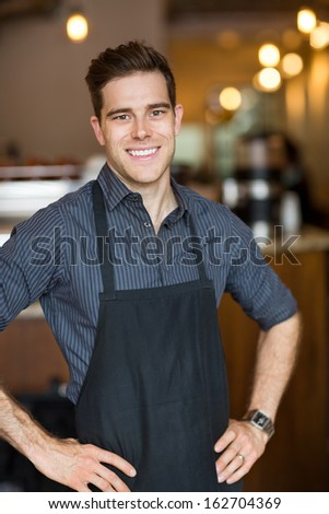 Portrait of happy male owner with hands on hips standing in cafe - stock photo