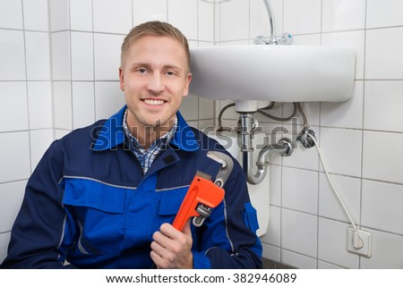 Portrait Of Happy Male Plumber Holding Wrench Sitting Next To Sink