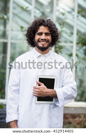 Portrait of happy male scientist holding digital tablet outside greenhouse