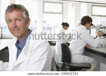 Portrait of happy male scientist with colleagues working in background - stock photo