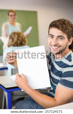 Portrait of happy male student holding paper in the class - stock photo
