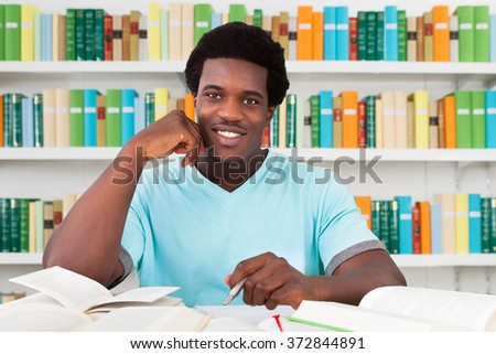 Portrait of happy male student sitting at desk in library