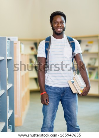 Portrait of happy male student with books standing in bookstore