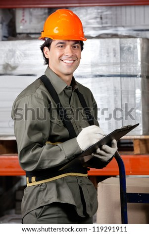 Portrait of happy male supervisor writing on clipboard at warehouse - stock photo
