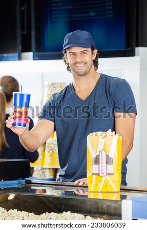 Portrait of happy male worker holding drink with popcorn at cinema concession stand while colleague working in background - stock photo