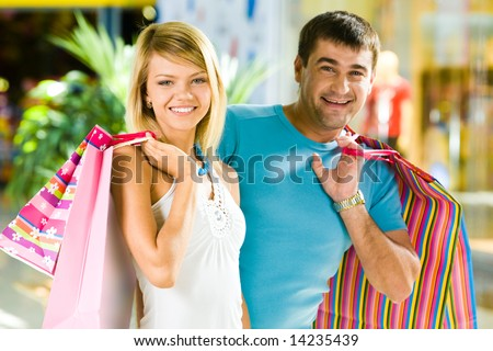 Portrait of happy man and woman with shopping bags in the mall - stock photo