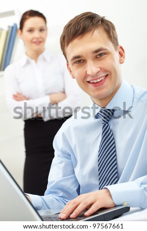 Portrait of happy man at workplace touching keys of laptop