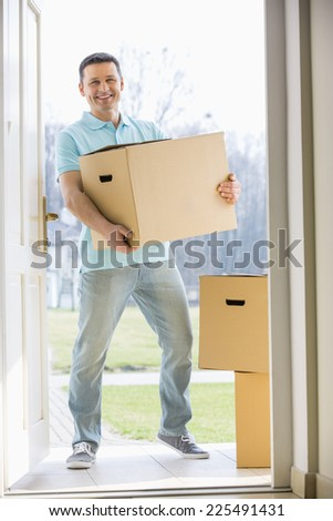 Portrait of happy man carrying cardboard box while entering new home - stock photo