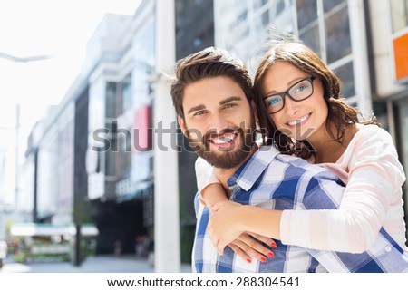 Portrait of happy man giving piggyback ride to woman in city - stock photo
