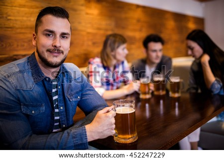 Portrait of happy man holding beer mug while friends in background at bar
