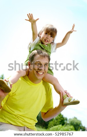 Portrait of happy man holding his little daughter on neck while having rest on summer day - stock photo