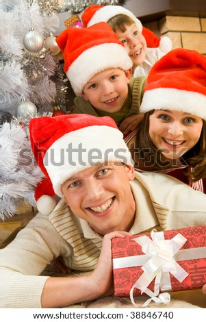 Portrait of happy man in Santa cap holding giftbox with his family on background - stock photo