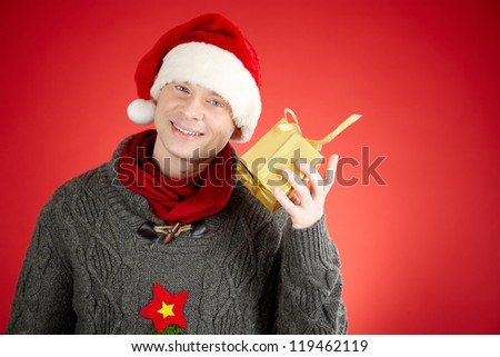 Portrait of happy man in Santa cap with giftbox by his ear looking at camera - stock photo