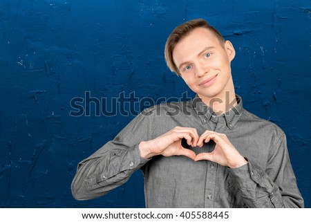Portrait of happy man making heart from his hands - stock photo