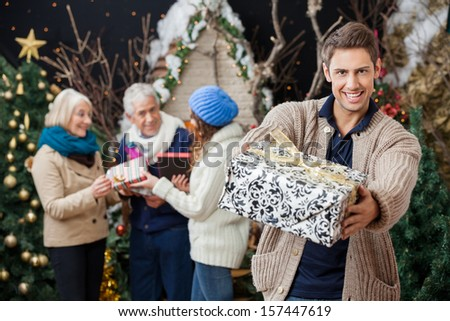 Portrait of happy man offering Christmas present with family standing in background at store - stock photo