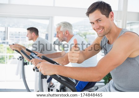 Portrait of happy man on exercise bike gesturing thumbs up at gym - stock photo