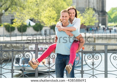 Portrait Of Happy Man Piggybacking His Wife - stock photo