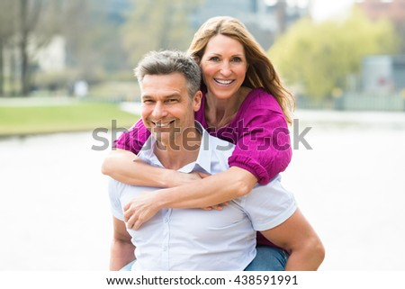 Portrait Of Happy Man Piggybacking His Wife