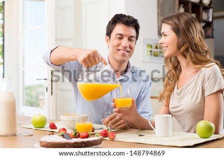 Portrait Of Happy Man Pouring Juice In Glass For Young Woman - stock photo