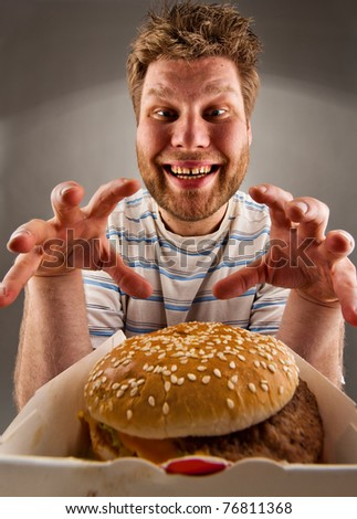 Portrait of happy man preparing to eat burger - stock photo