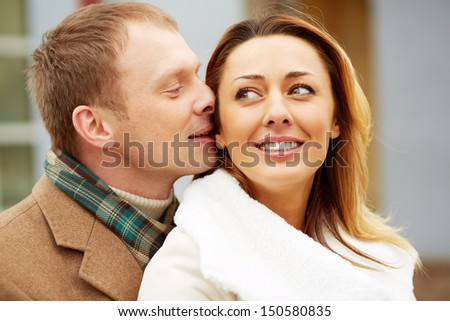 Portrait of happy man whispering something into his girlfriend ear - stock photo