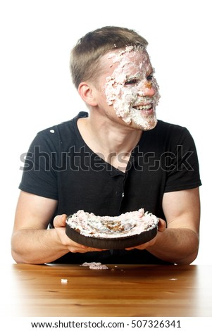 Portrait of happy man with cake on his face