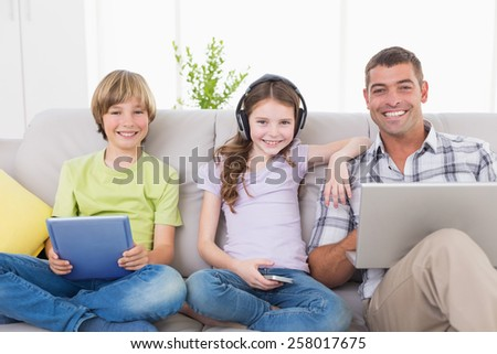 Portrait of happy man with children using technologies while sitting on sofa at home - stock photo
