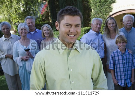 Portrait of happy man with family standing in background