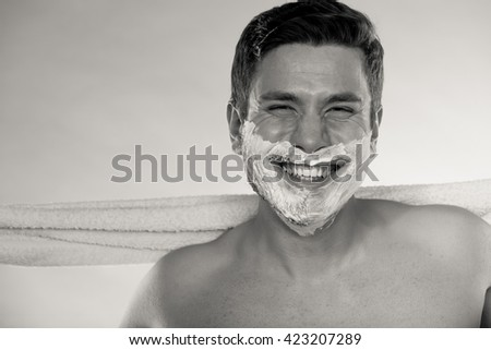 Portrait of happy man with half shaved face beard hair. Smiling handsome guy on blue. Skin care and hygiene. Black and white photo. - stock photo