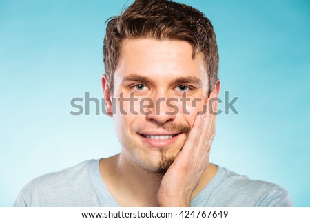 Portrait of happy man with half shaved face beard hair. Smiling handsome guy on blue. Skin care and hygiene. - stock photo