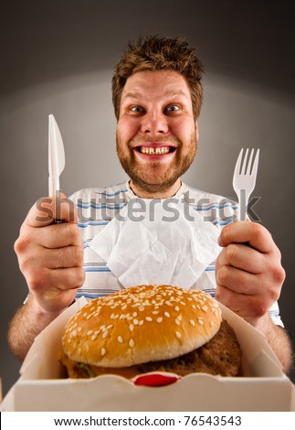 Portrait of happy man with knife and fork ready to eat burger - stock photo