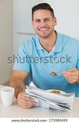 Portrait of happy man with newspaper having breakfast at table in kitchen - stock photo